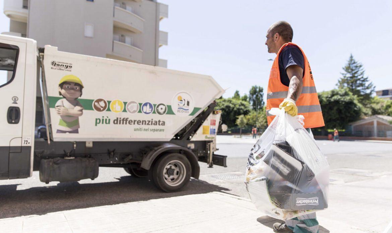 operatore ecologico preleva sacchetto rifiuti per la raccolta della carta