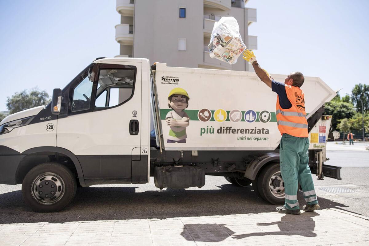 operatore ecologico getta sacchetto rifiuti nel furgone della raccolta differenziata