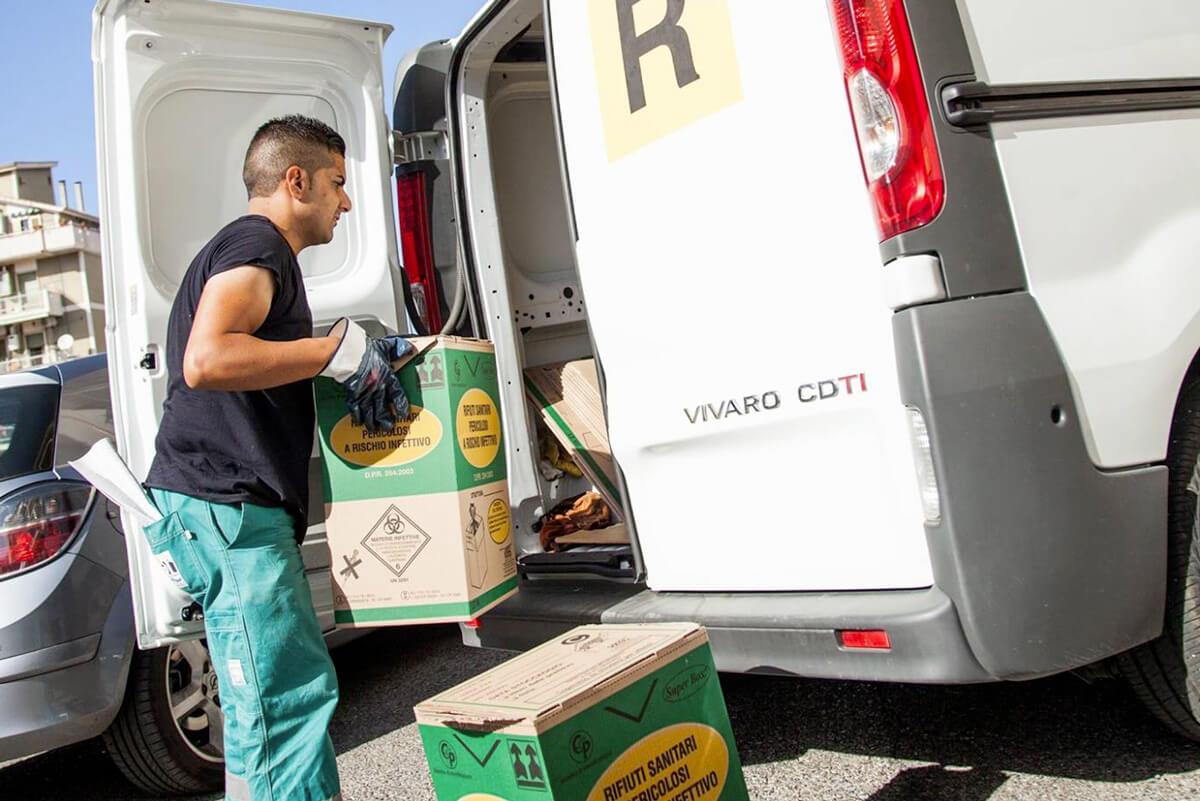 operatore ecoross carica sul furgoncino contenitori dei rifiuti sanitari