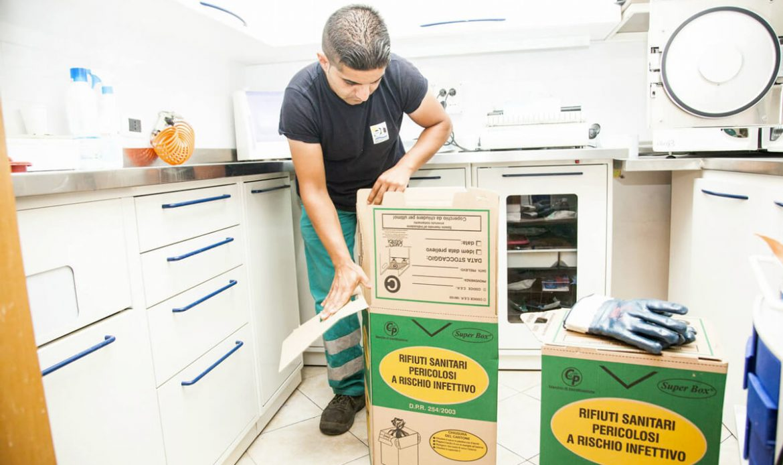 operatore ecoross preleva contenitore rifiuti sanitari